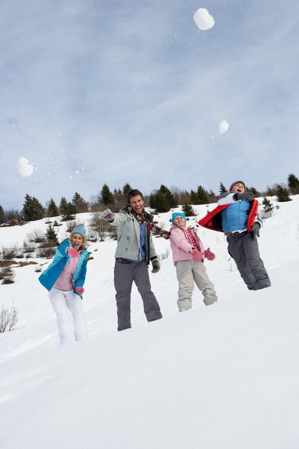 Boules de neige de projection de jeune famille des vacances de l'hiver image stock