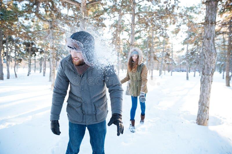 Boules de neige thowing de femme joyeuse chez l'homme bel photographie stock libre de droits