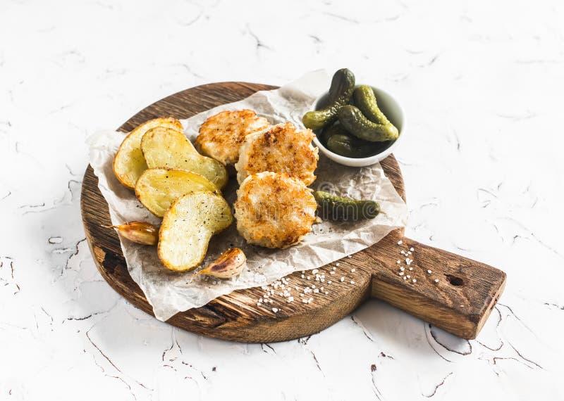 Boules de poissons et pommes de terre cuites au four sur la planche à découper en bois photographie stock