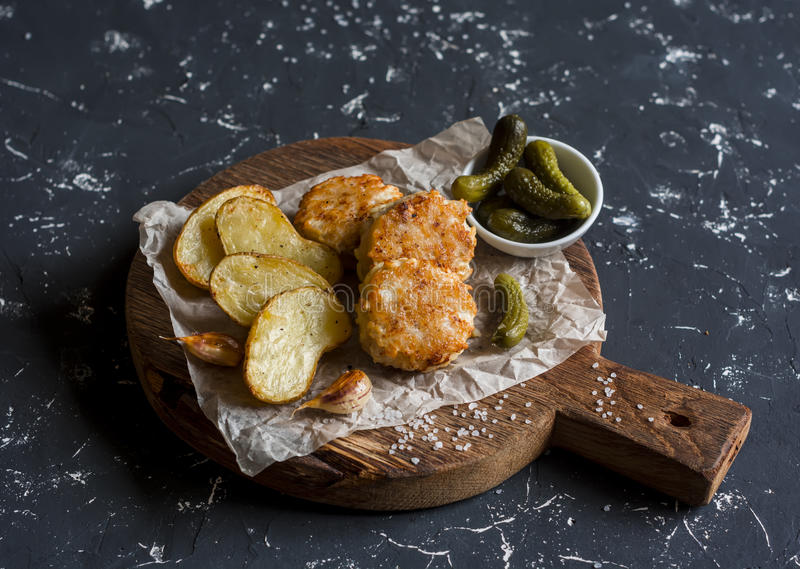 Boules de poissons et pommes de terre cuites au four sur la planche à découper en bois photo libre de droits