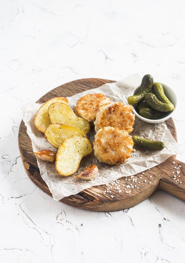 Boules de poissons et pommes de terre cuites au four sur la planche à découper en bois image libre de droits