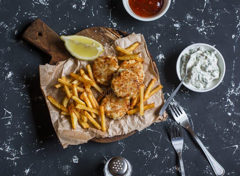 Boules de poissons, pommes chips, sauces sur un fond foncé images libres de droits