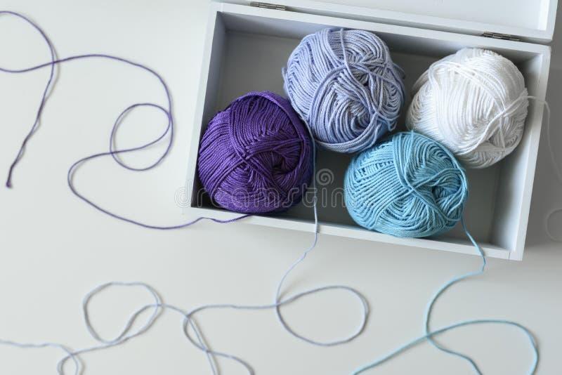 Boules de tricotage colorées dans une boîte en bois blanche sur la table avec des brins autour image libre de droits