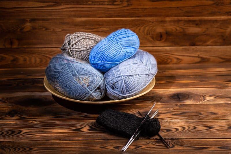Boules des fils gris et bleus dans un plat en bois et des aiguilles de tricotage avec le mod?le de tricotage sur un fond en bois photos libres de droits