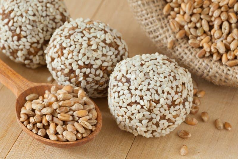 Boules des pousses moulues de blé avec les graines de sésame images libres de droits