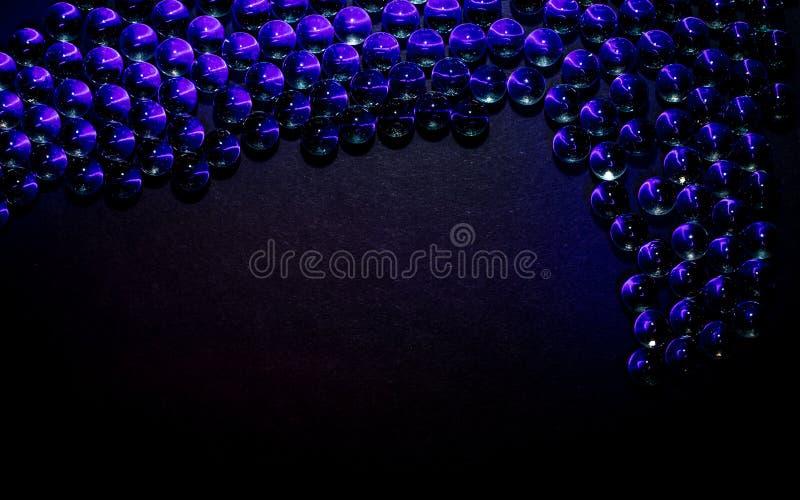 Boules en verre sur un fond noir avec la lumière UV image stock