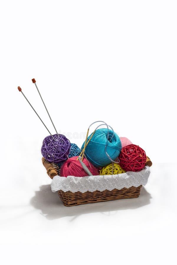 Boules et aiguilles de tricotage de fil de couleur dans le panier d'isolement sur le fond blanc photographie stock