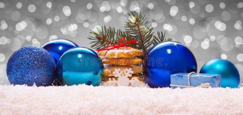 Boules et biscuits bleus de Noël sur la neige photo libre de droits