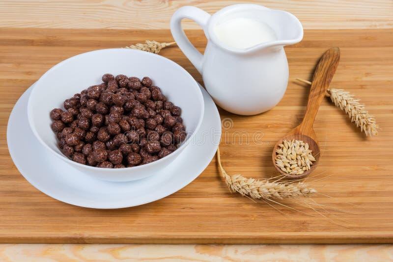 Boules et lait de chocolat de c?r?ale de petit d?jeuner parmi des oreilles et des grains image libre de droits