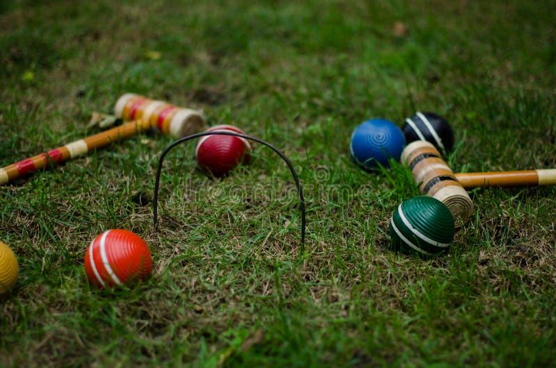 Boules et maillets de croquet sur l'herbe image stock