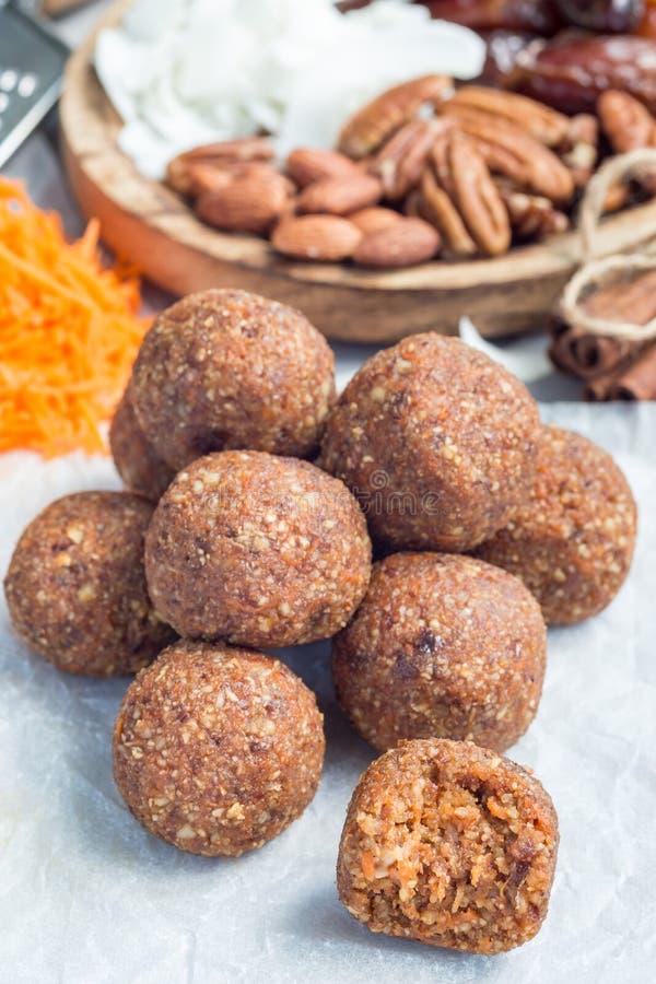 Boules faites maison saines d'énergie de paleo avec la carotte, les écrous, les dates et les flocons de noix de coco, sur la vert photos libres de droits