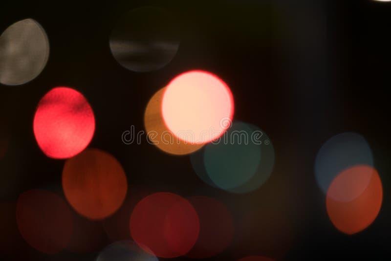 Boules multicolores abstraites de bokeh flottant à travers un fond foncé photos libres de droits