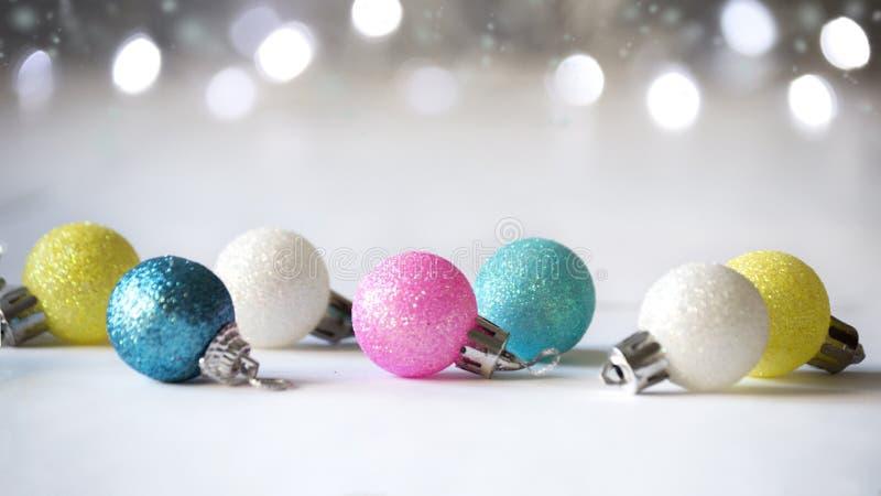 Boules multicolores sur l'arbre de Noël sur un fond clair avec le bokeh photos stock