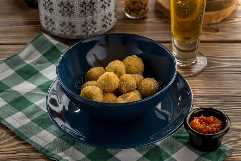 Boules ou croquettes frites de fromage de pomme de terre avec le ketchup de tomate et le verre de bière sur la table en bois images libres de droits