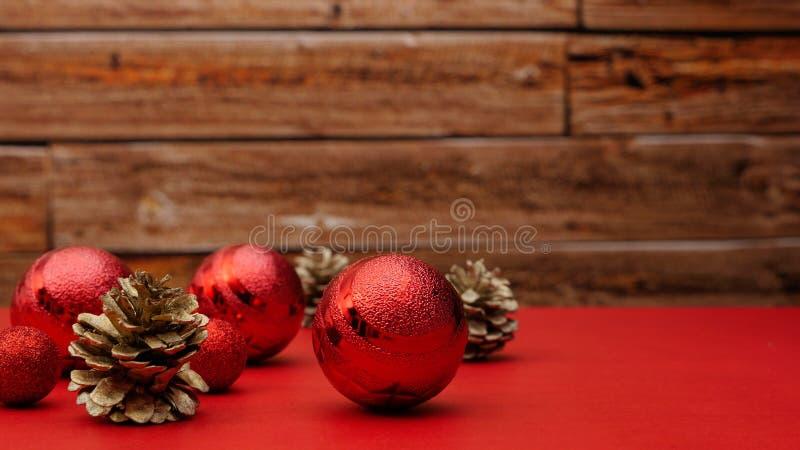 Boules rouges d'arbre de Noël et cônes de sapin d'or se trouvant sur une table rouge de fête images stock