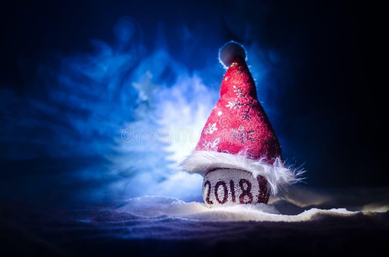 Boules rouges de Noël avec 2018 nombre et chapeau du père noël sur le fond naturel de neige Concept 2018 de bonne année Copiez l' image libre de droits