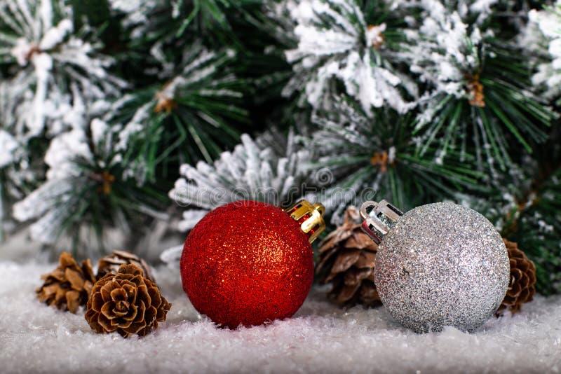 Boules rouges et argentées de décoration de Noël dans un arbre avec la tresse et pinecone dans la neige photos libres de droits