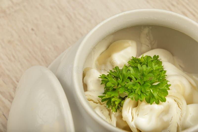 Boulettes dans un pot blanc avec la crème sure et verts sur un fond en bois photo stock
