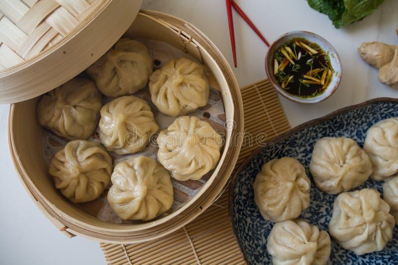 Boulettes de dim sum aka, momos dans un vapeur en bambou traditionnel, avec les baguettes rouges, le chou de chine et la racine d image libre de droits