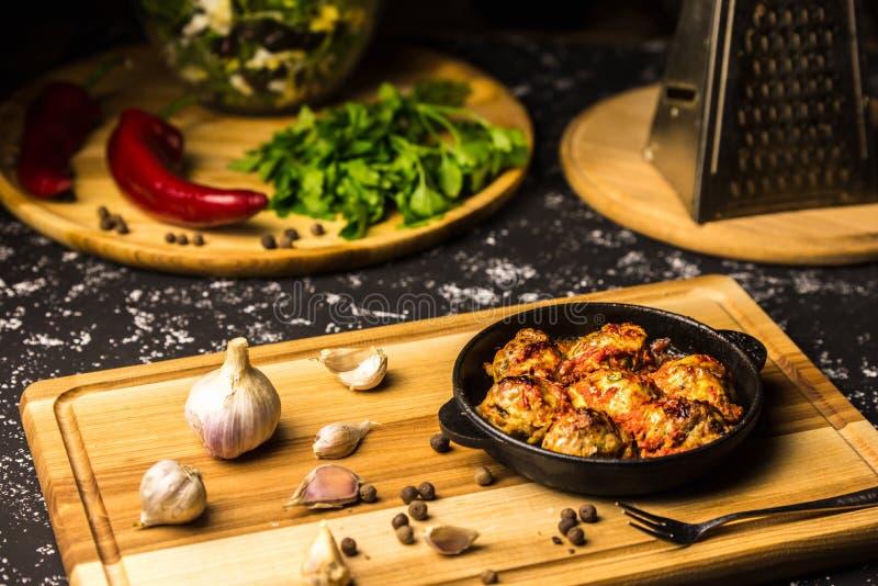 Boulettes de viande dans une casserole de fer sur un conseil en bois avec l'ail et les grains de poivre photo stock