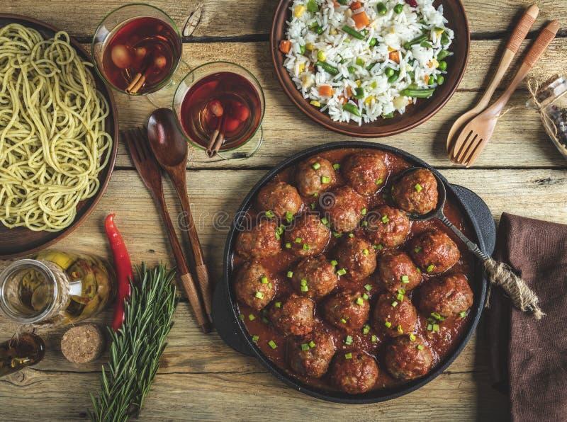 Boulettes de viande faites maison en sauce tomate Poêle sur une surface en bois, riz avec des légumes, pâtes image libre de droits