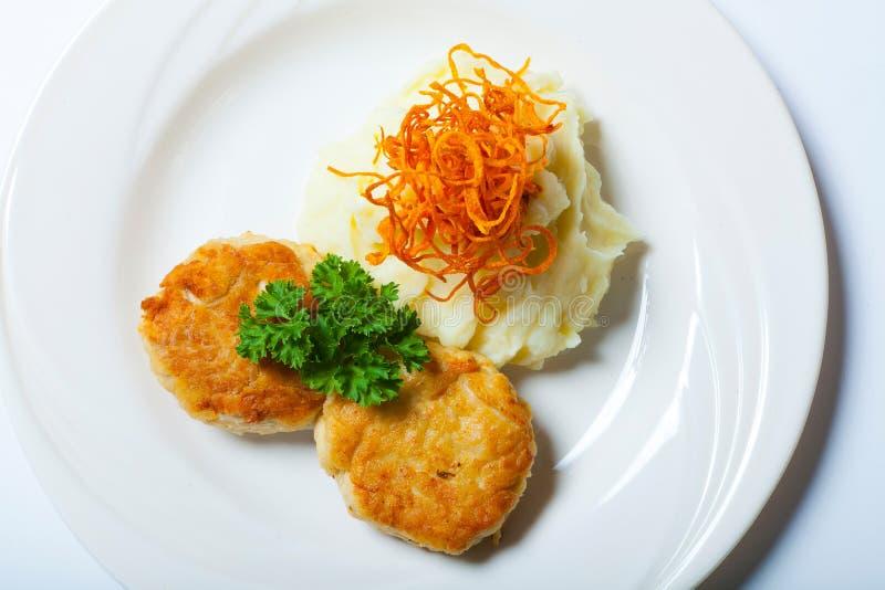 Boulettes de viande frites faites maison avec de la purée de pommes de terre sur la fin blanche de plat  photos stock