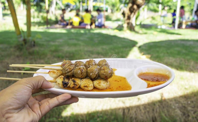 Boulettes de viande grillées de porc et de boeuf avec de la sauce à fruits de mer sur les touristes troubles de fond en plastique images libres de droits