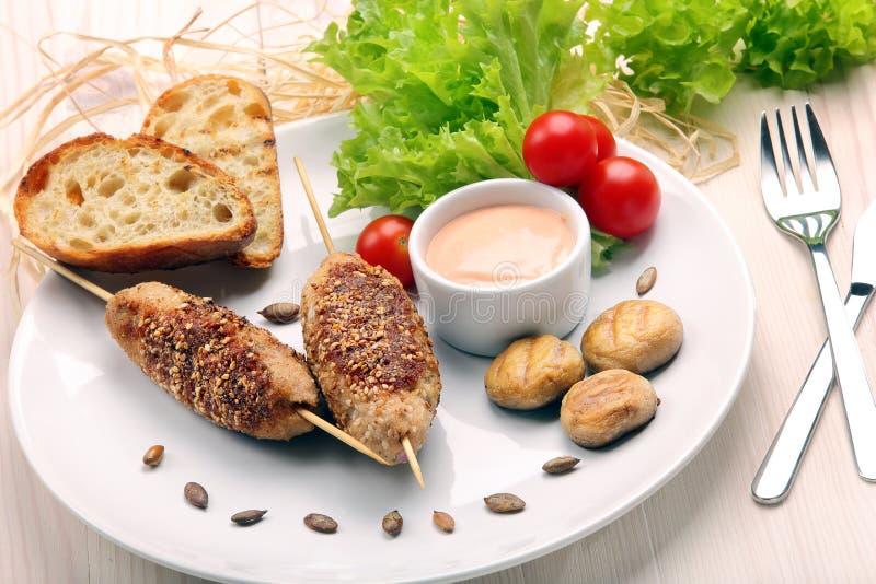 Boulettes de viande hachées cuites au four comme brochettes avec les graines de sésame photographie stock libre de droits