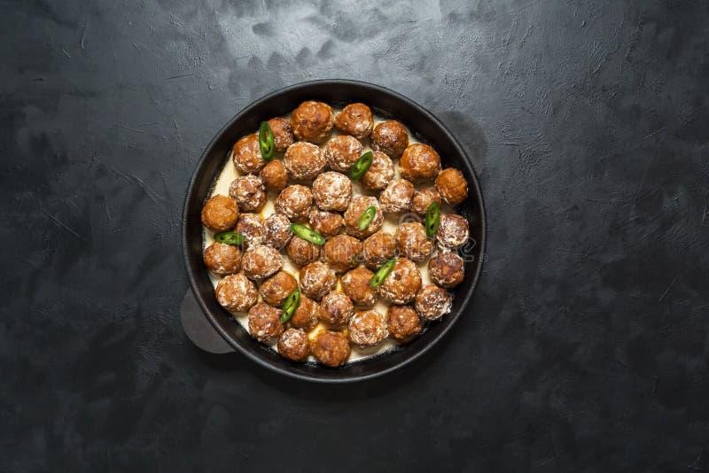 Boulettes de viande juteuses dans une poêle sur une table noire photo libre de droits