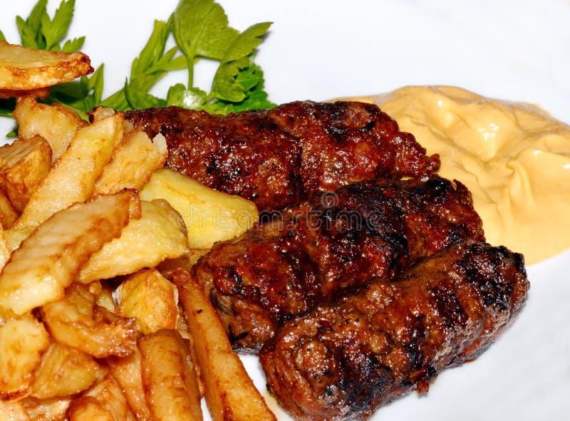 Boulettes de viande roumaines ou Mici et Fried Chips images libres de droits
