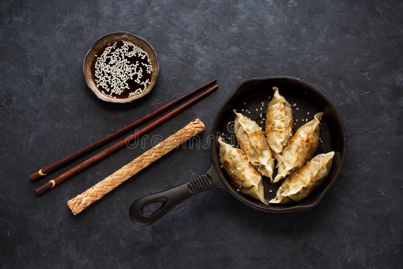 Boulettes frites Gyoza dans une poêle avec la sauce de soja, et les baguettes photographie stock