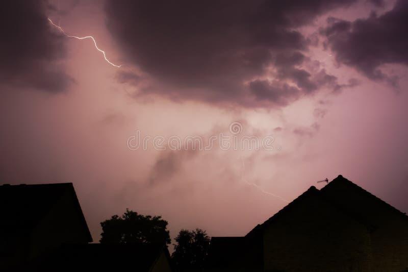 Boulon d'allégement au-dessus des maisons au milieu d'une tempête photos libres de droits