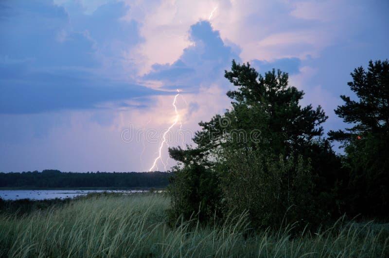 Boulon de foudre heurtant la terre avec des arbres et le bord de la mer dans le premier plan photographie stock