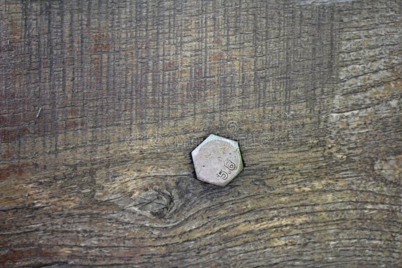 Boulon en acier dans un vieux conseil en bois images stock