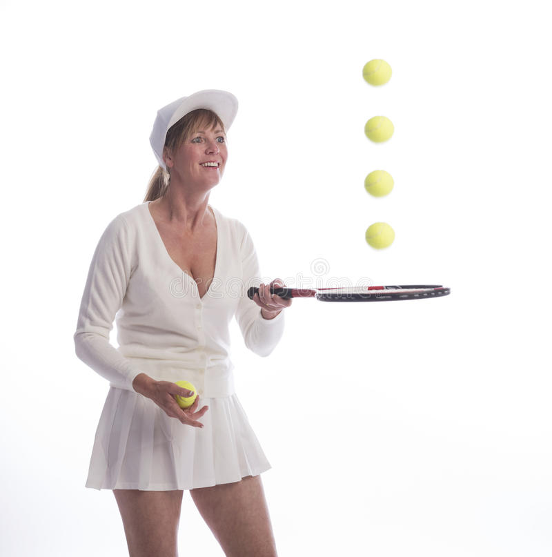 Bouncing tennis balls on a racket. Woman tennis player with a racquet and bouncing balls stock photography