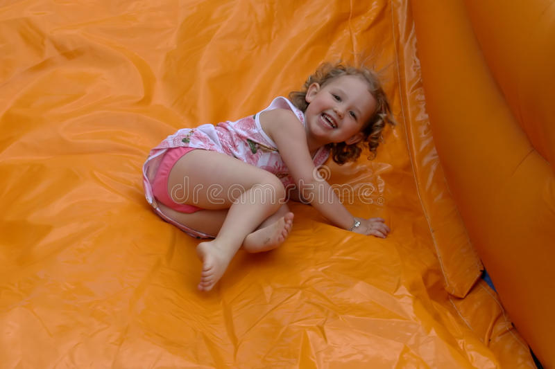 Bouncy castle with laughing girl stock images