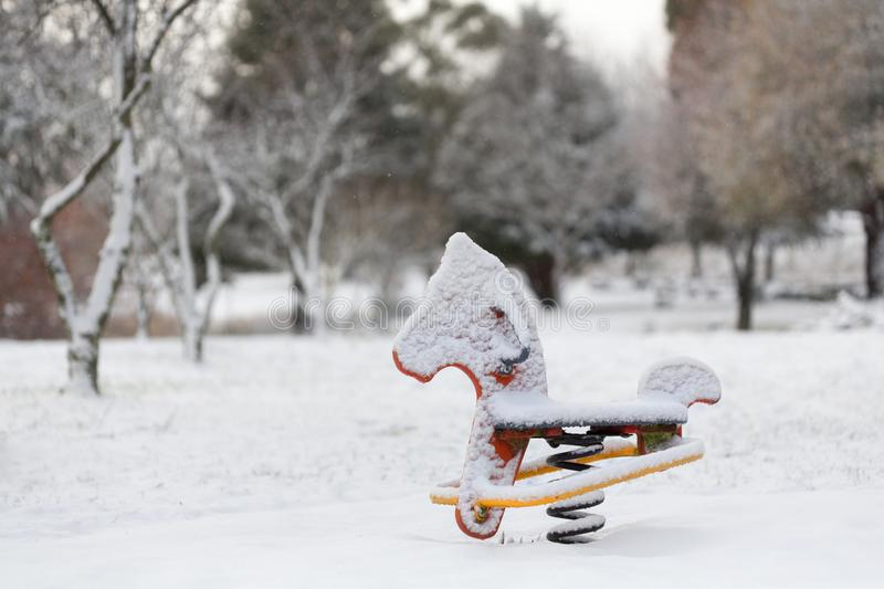 Playground equipment rocking horse covered in snow. A bouncy rocking horse child`s playground equipment covered in fresh snow in a park in Oberon rural Australia stock photography