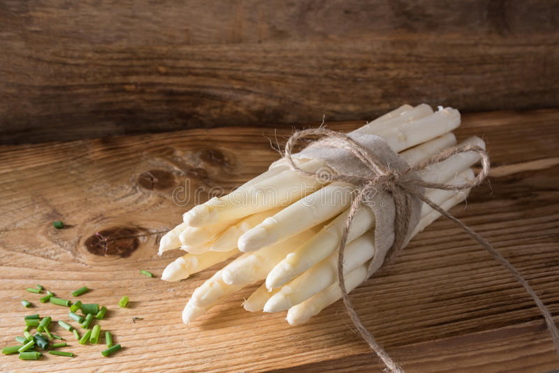Bound asparagus on a wooden board stock photos