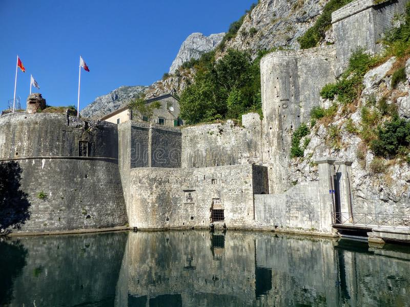 Boundaries of a fortress around the city of Kotor in Montenegro with its reflex on the water, Kotor, Montenegro. royalty free stock photos