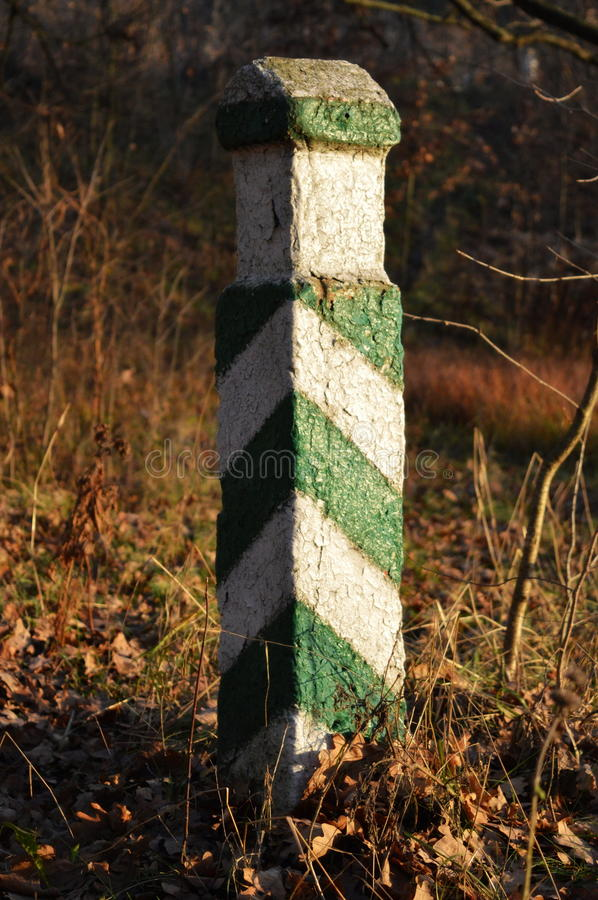 Boundary pillar. Concrete green and white boundary pillar in the autumn forest stock images
