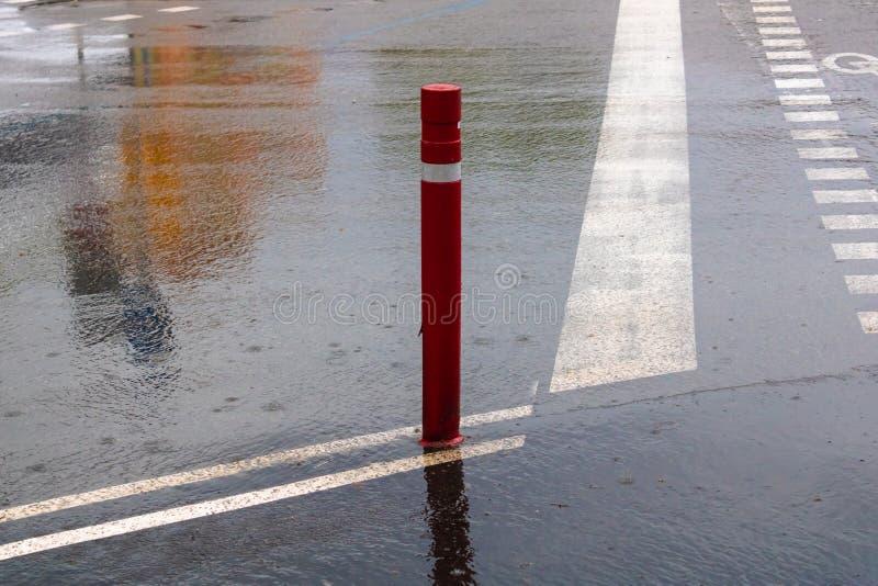 Boundary pillar on the rainy day, red traffic pole. Image royalty free stock photo