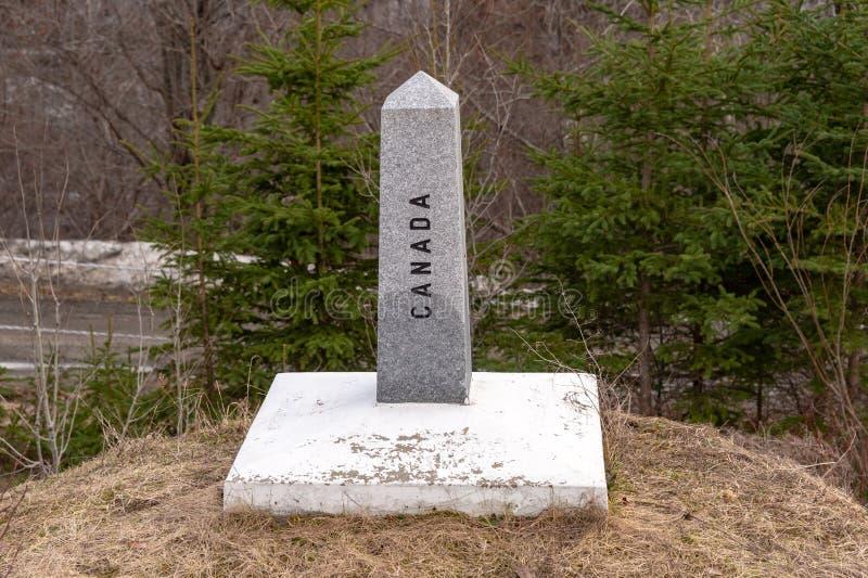 A boundary stone marks the US/Canada border stock image