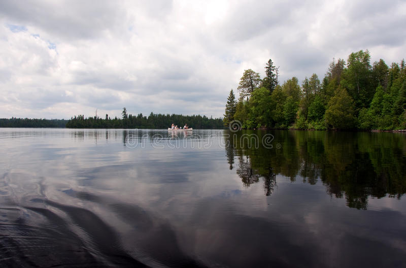 Boundary Waters Canoeing. Wideshot of a lake in the Boundary Waters, Minnesota. Sky, clouds, trees and canoe reflected royalty free stock photo