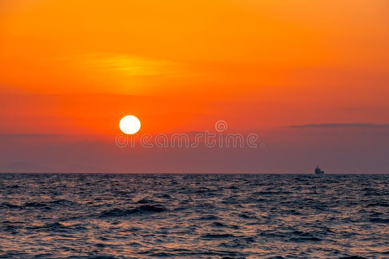 Boundless Sea and Sunset. Boundless sea. Unbelievable red sunset. Small freighter ship on the horizon stock photo