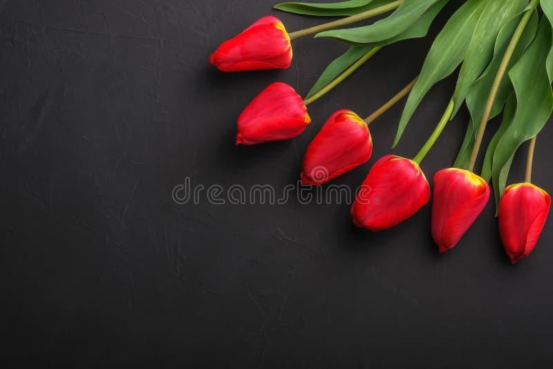 Bouqet de tulipanes rojos en fondo negro con el espacio de la copia para el texto imagen de archivo libre de regalías
