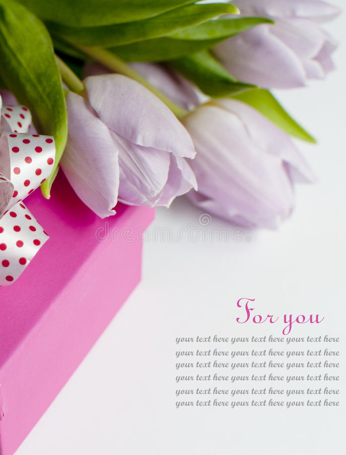 Bouqet tulips and gift on the white background. Mothers day pink gift and bouqet of tulips royalty free stock photo