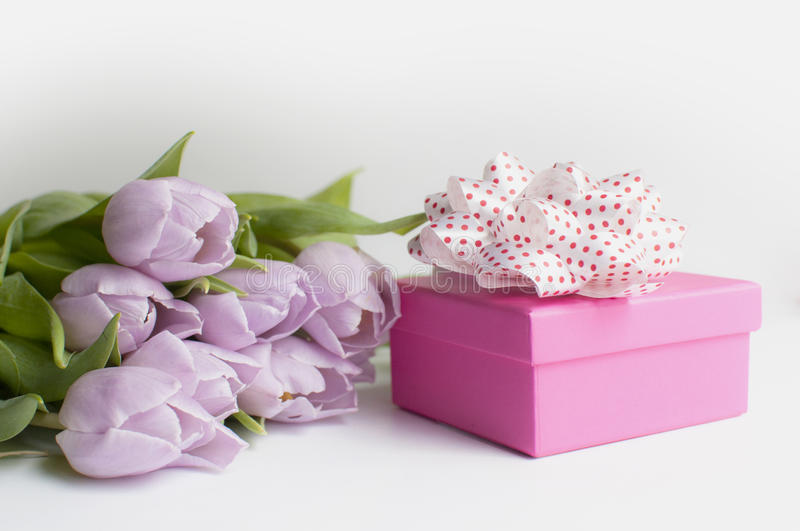 Bouqet tulips and gift on the white background. Mothers day pink gift and bouqet of tulips royalty free stock images