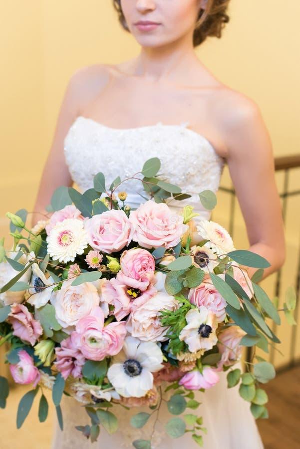 Bouquet énorme dans de jeunes mains du ` s de jeune mariée photographie stock