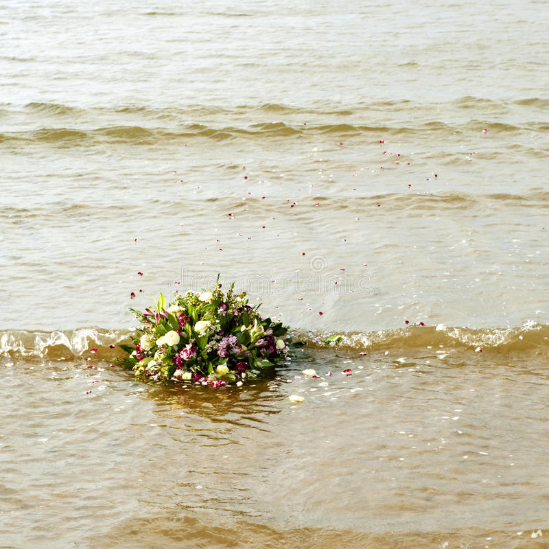 Bouquet afloat. In the gentile surf of the north sea, as metaphor of remembrance of a watery grave royalty free stock photo