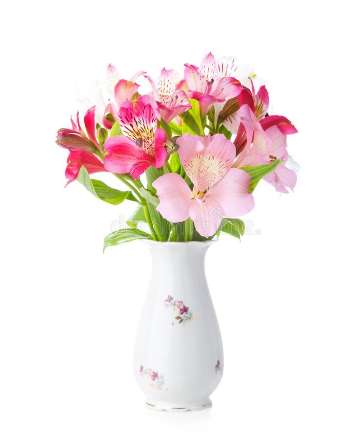 Bouquet of Alstroemeria flowers in old porcelain vase isolated on white background stock photo